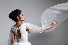 白色婚礼服礼服的w可爱的亚裔美丽的妇女新娘 库存图片