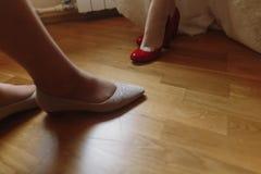 白色婚礼礼服的投入在红色鞋子的,腿美丽的新娘 图库摄影