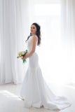 白色婚礼礼服的新娘与花花束  免版税库存图片