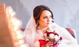 白色婚礼礼服的美丽的新娘与新娘花束 免版税库存图片