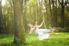白色婚礼礼服的美丽的新娘微笑和摇摆在森林里的 免版税库存图片