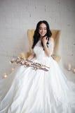 白色婚礼礼服的被晒黑的美丽的深色的新娘坐椅子 在拿着棉花分支的手上 免版税库存图片