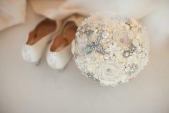 白色婚礼鞋子和现代婚礼花束 库存图片