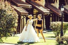 白色婚纱和性感的适合的女孩的俏丽的新娘 免版税库存照片