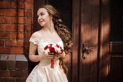 白色婚纱的美丽的新娘有在木门附近的一个婚姻的花束身分的 图库摄影