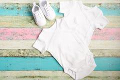 白色婴孩onesie和运动鞋在淡色木背景 好为插入物您的设计 嘲笑 库存图片