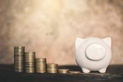 白色存钱罐和硬币在木头 免版税图库摄影