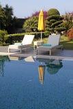 白色室外家具和黄色伞在游泳的po附近 库存图片
