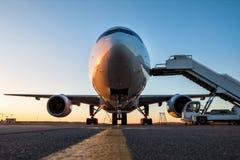 白色宽身体乘客飞机正面图有的在机场围裙的上的台阶在平衡的太阳 免版税库存照片