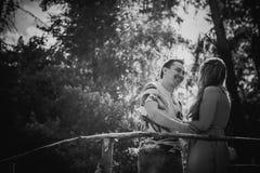 黑白色对桥梁的摄影浪漫年轻夫妇亲吻和立场在背景 免版税库存照片