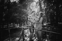 黑白色对桥梁的摄影浪漫年轻夫妇亲吻和立场在背景 库存图片