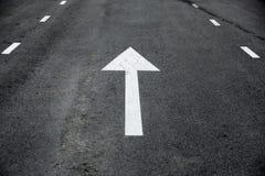 白色对路的箭头直直往前的交通标志透视 免版税图库摄影