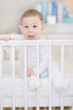 白色小儿床的逗人喜爱的婴孩-一个可爱的孩子的portait 免版税图库摄影