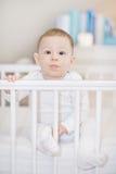 白色小儿床的逗人喜爱的婴孩-一个可爱的孩子的portait 库存照片