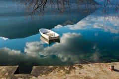 白色小船在天空明白水中 免版税图库摄影