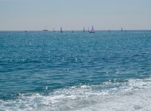 白色小船航行在开放蓝色海 库存照片