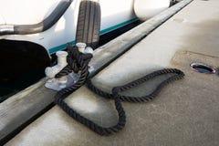 白色小船被栓对有一条黑绳索的码头 免版税库存图片