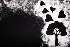 白色小麦面粉的典雅的图片和与心脏的一棵树在黑背景 免版税图库摄影