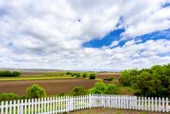 白色尖桩篱栅、农田和云彩 免版税库存照片