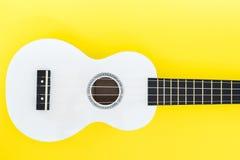 白色尤克里里琴在黄色背景和有文本的一个地方的 音乐概念 平的位置 免版税库存照片