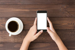 给白色屏幕打电话在台式的妇女手上 免版税库存照片