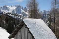 白色山和一个小小屋的屋顶在冬天 免版税图库摄影