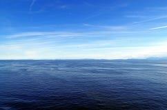 白色山和蓝天在海洋 库存图片