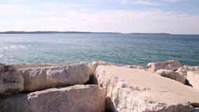 白色岩石和石头与蓝色海和天空在风景背景中 美丽的白色岩石向海滩扔石头 股票录像