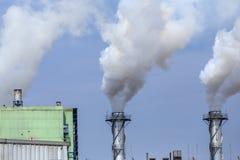 白色工业蒸汽在蓝天的工厂 免版税库存照片