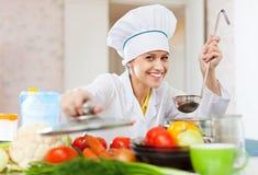 白色工作服的愉快的厨师在厨房里工作 免版税图库摄影