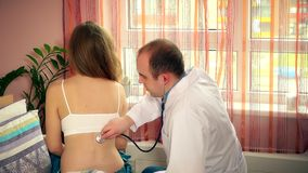 白色工作服的仔细的人医生审查年轻女性妇女患者的 股票录像