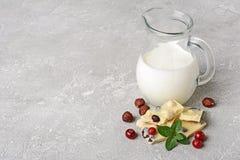 白色巧克力块用整个榛子,蔓越桔andï ¿牛奶½水罐特写镜头片断  免版税库存图片