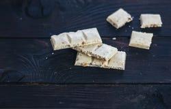 白色巧克力用榛子和蔓越桔在黑暗的木头 免版税库存照片