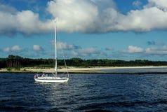 白色帆船进行中使用引擎移动向外去 背景是海滩 图库摄影