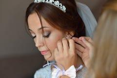 白色帮助与婚礼准备的礼服和她的朋友的时髦的美丽的深色的新娘 库存图片