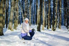 白色帽子和围巾的愉快的女孩做看照相机的一个雪球 浅黑肤色的男人使用户外  图库摄影
