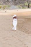 白色帽子和礼服的赤足女孩走在海滩的 免版税库存照片