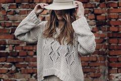 白色帽子和boho白色毛线衣posin的时髦的深色的妇女 免版税库存图片