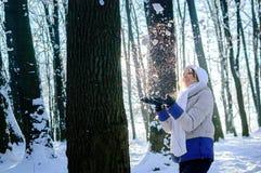 白色帽子的俏丽的女孩和围巾吹从她的手的雪在晴朗的天气期间在冬天 免版税图库摄影