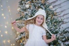 白色帽子的女孩在圣诞树下 免版税库存图片