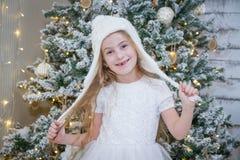 白色帽子的女孩在圣诞树下 库存图片