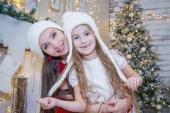 白色帽子的女孩有母亲的在圣诞树下 库存照片