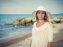 白色帽子的美丽的妇女在大石头背景在海滩的 库存照片