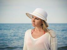 白色帽子的美丽的妇女有在海的背景的流动的头发的 库存照片