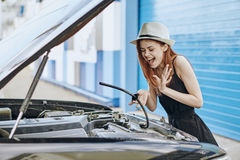 白色帽子的年轻美丽的妇女修理在街道上的一辆汽车 库存照片