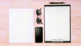白色干净的纸片与一支稀薄的黑笔、一个大黑智能手机和玻璃的在一张浅褐色的木桌上 库存图片