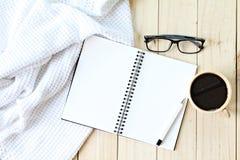 白色平的位置编织了毯子、镜片、咖啡和在木背景的空白的笔记本纸 免版税库存照片