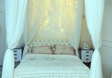 白色床和光亮的光在卧室 图库摄影