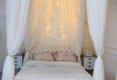 白色床和光亮的光在卧室 免版税库存图片
