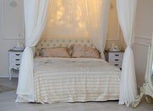 白色床和光亮的光在卧室 免版税库存照片